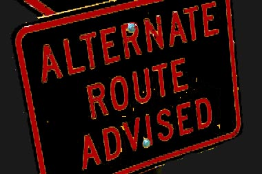 Black road sign with red text: Alternate route advised.