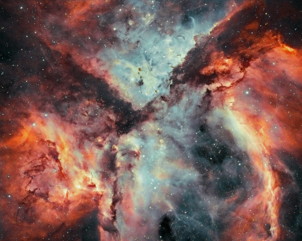 Close up of the Carina Nebula that looks like vividly coloured clouds full of stars.